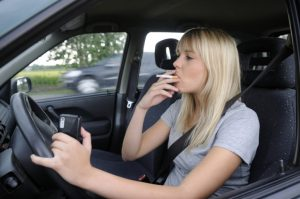Woman driving and smoking with cellphone